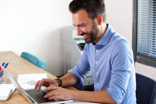 Smiling mature business man working on laptop