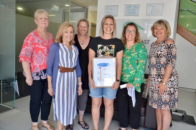 "Michelle Bradbury (right), CEO of Central Coast Primary Care and staff present the ""Viewer's Choice Award"" to Katie Dobson – Modern Abstract Artist (Centre)."