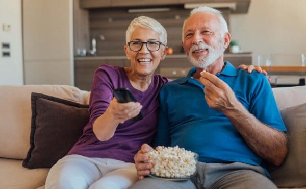 Couple together eating popcorn and watching a movie
