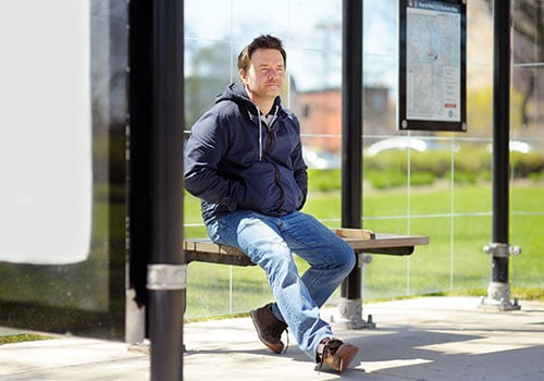 Health on The Streets. A man waiting at a bus stop